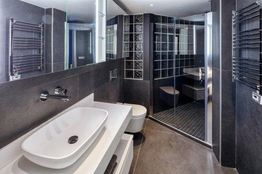 Baño con ducha de obra y pared de  pavés. Lavabo Corian